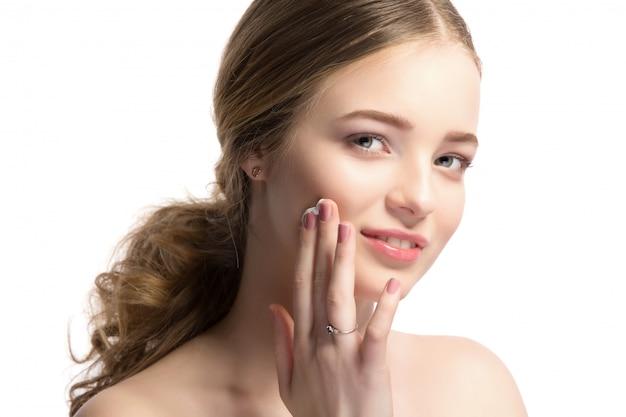 Retrato de mulher loira bonita, aplicar creme no rosto