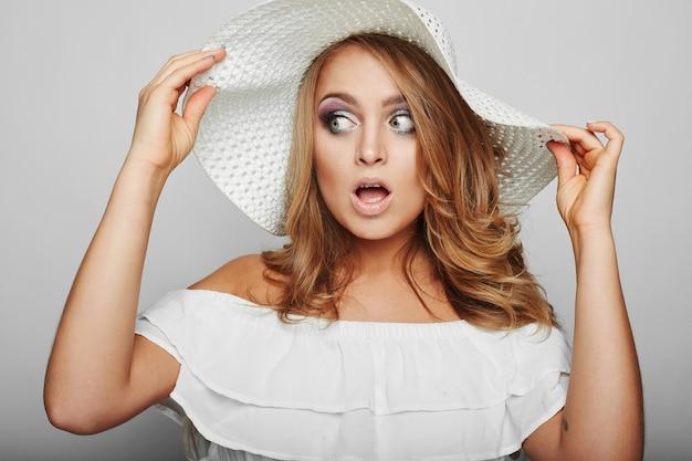Retrato de mulher loira bonita no vestido branco do verão