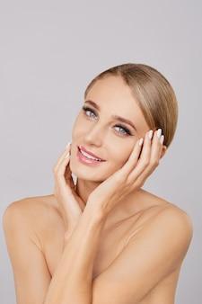 Retrato de mulher loira bonita sorridente com maquiagem natural tocando seu rosto.