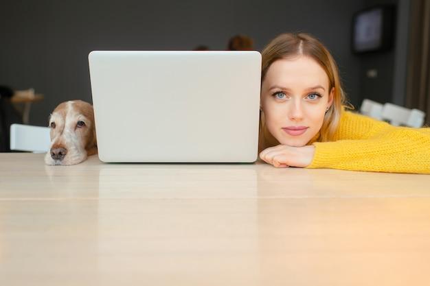 Retrato de mulher loira cabeça e cabeça de seu cachorro cocker spaniel deitado juntos em uma mesa ao longo das bordas do laptop