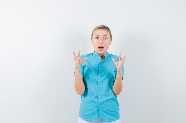 Retrato de mulher loira com as mãos levantadas na blusa azul isoladas