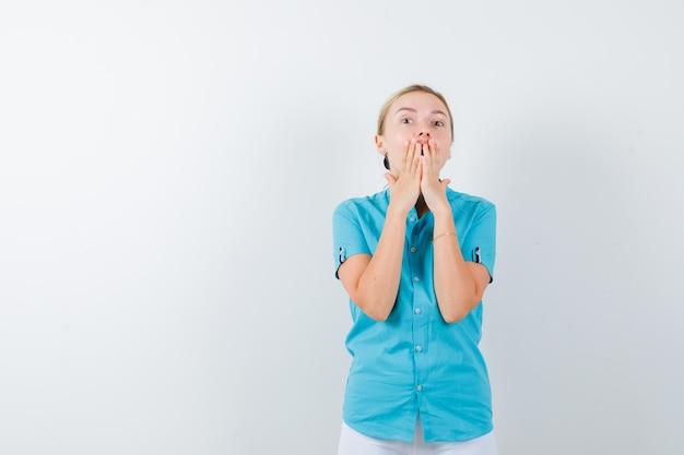 Retrato de mulher loira com as mãos na boca na blusa azul isolada