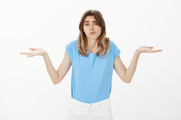Retrato de mulher loira confusa encolhendo os ombros e parecendo indecisa, não sei de nada
