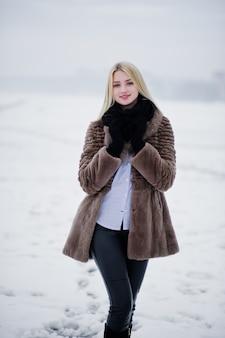Retrato de mulher loira elegância jovem em um casaco de pele, rio nevoento no gelo do inverno.