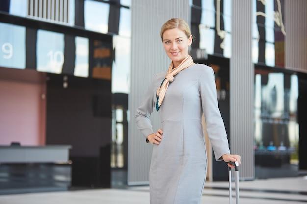 Retrato de mulher loira elegante com mala e sorrindo enquanto posava no aeroporto,