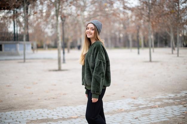 Retrato de mulher loira jovem sorridente feliz com chapéu de inverno em um parque no outono