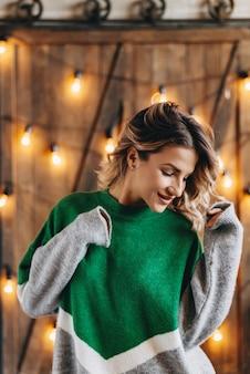 Retrato de mulher loira moderna dança em uma camisola contra um fundo de luzes e uma parede de madeira