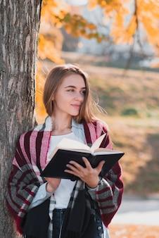 Retrato de mulher loira segurando um caderno