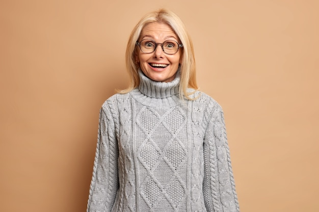 Retrato de mulher loira sênior feliz e surpresa com aparência europeia parece alegremente usando óculos e suéter cinza quente expressa maravilha ouve notícias agradáveis do interlocutor
