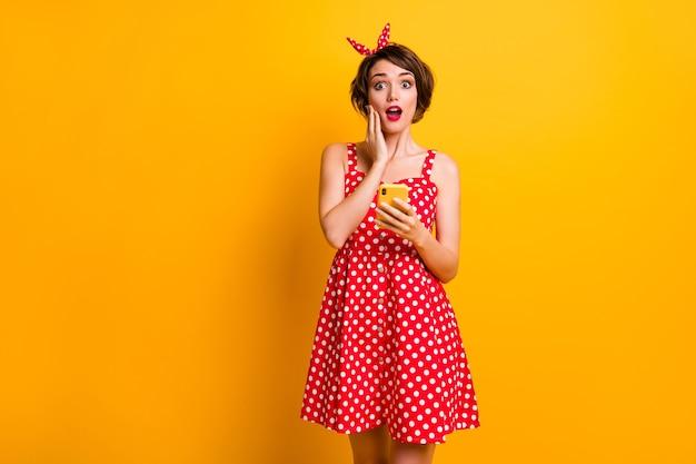 Retrato de mulher louca atônita, usar telefone inteligente, ler informações da rede social impressionado gritar wow omg usar roupas de boa aparência isoladas sobre parede de cor amarela