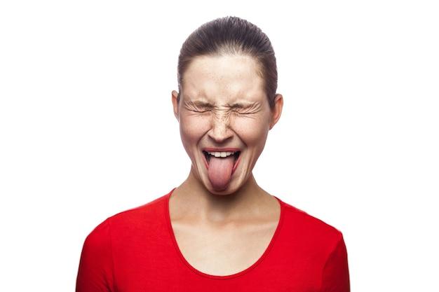 Retrato de mulher louca e engraçada em camiseta vermelha com sardas e língua