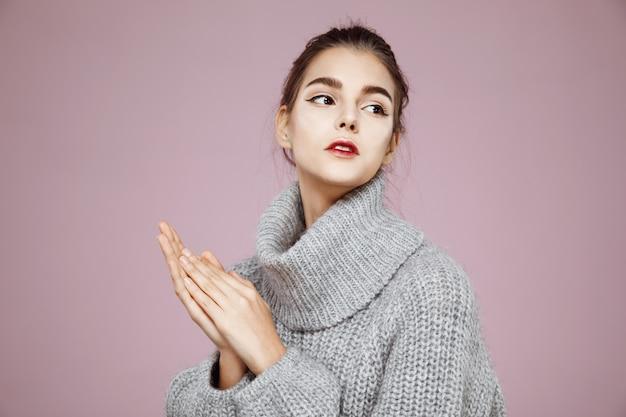 Retrato de mulher macia no suéter cinza aquecimento as mãos no espaço da cópia-de-rosa