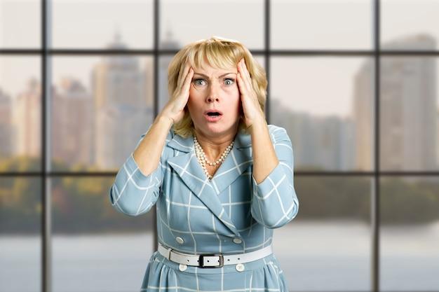 Retrato de mulher madura atônita. closeup retrato de uma mulher apavorada olhando chocado e surpreso em total descrença com as mãos na cabeça, janela do escritório.