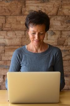 Retrato de mulher madura bonita usando laptop em uma mesa de madeira contra a parede de tijolos