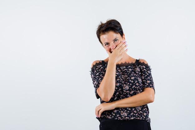 Retrato de mulher madura cobrindo a boca com a mão na blusa e olhando de frente com alegria