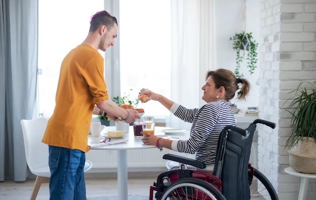 Retrato de mulher madura com deficiência em cadeira de rodas, sentada à mesa com um filho dentro de casa