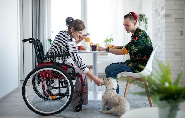 Retrato de mulher madura com deficiência em cadeira de rodas, sentada à mesa com um filho e um cão dentro de casa