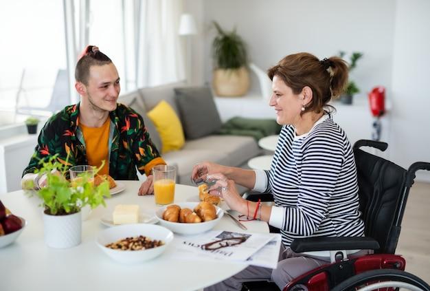 Retrato de mulher madura com deficiência em cadeira de rodas, sentada à mesa