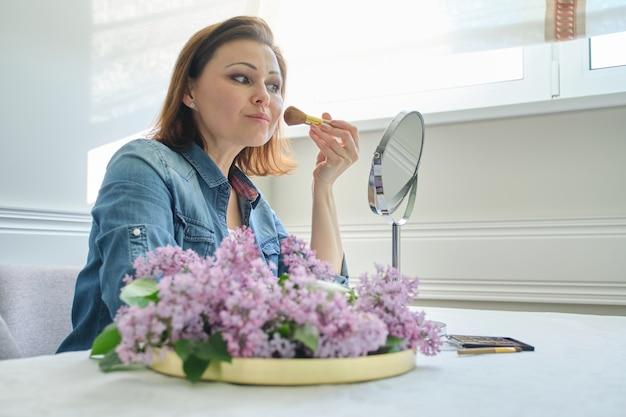 Retrato de mulher madura com espelho de maquiagem, linda fêmea 40 anos