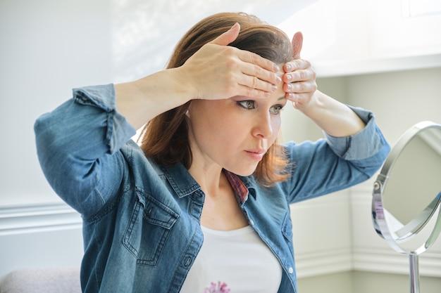 Retrato de mulher madura com espelho de maquiagem massageando o rosto