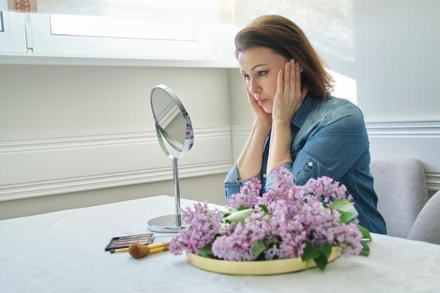 Retrato de mulher madura com espelho de maquiagem massageando seu rosto e pescoço