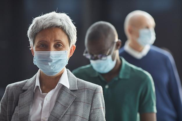 Retrato de mulher madura com máscara protetora olhando em pé na fila