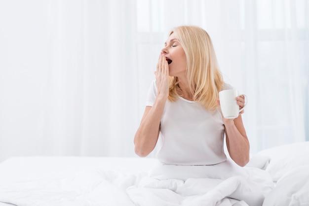 Retrato de mulher madura com sono segurando uma xícara