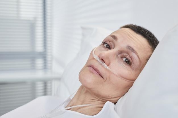 Retrato de mulher madura deitada na cama e tratando no hospital