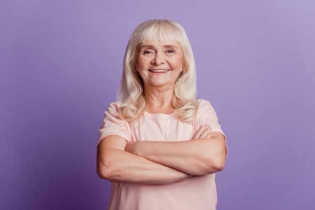 Retrato de mulher madura e alegre em pé com os braços cruzados sobre fundo violeta