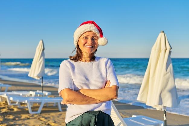 Retrato de mulher madura e feliz com chapéu de papai noel na estância balnear da praia