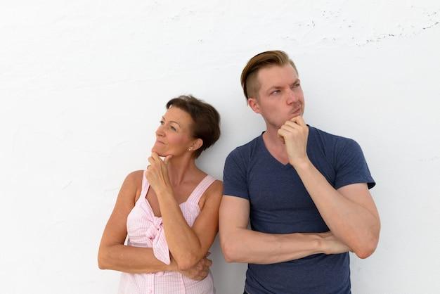 Retrato de mulher madura e jovem como mãe e filho juntos contra uma parede branca como uma parede ao ar livre