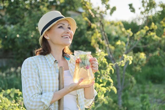 Retrato de mulher madura feliz no chapéu no jardim com bebida herbal natural caseira com morangos hortelã