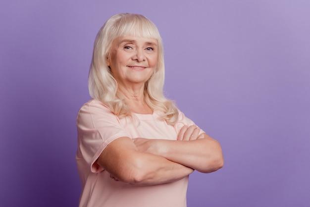 Retrato de mulher madura idosa com os braços cruzados sobre fundo violeta