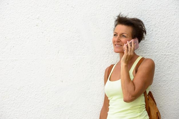 Retrato de mulher madura linda turista contra uma parede branca ao ar livre
