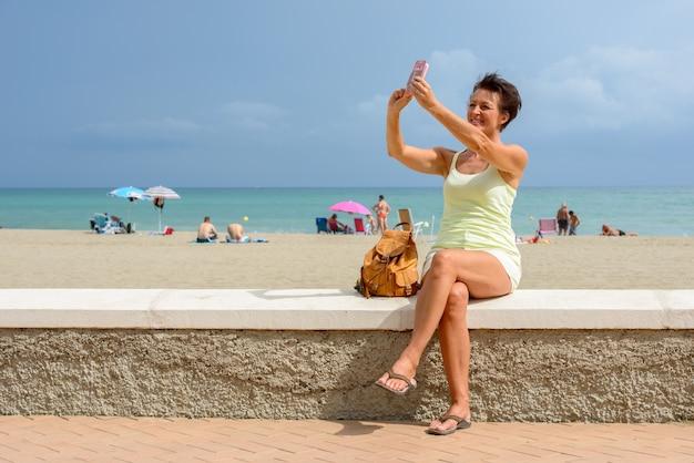 Retrato de mulher madura linda turista na praia ao ar livre