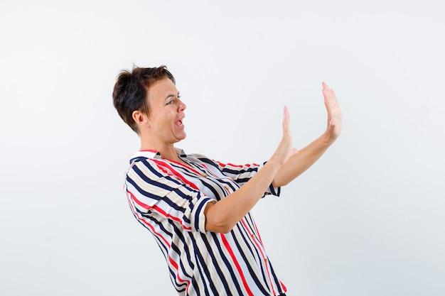 Retrato de mulher madura mostrando um gesto de parada com uma camisa listrada e olhando com medo
