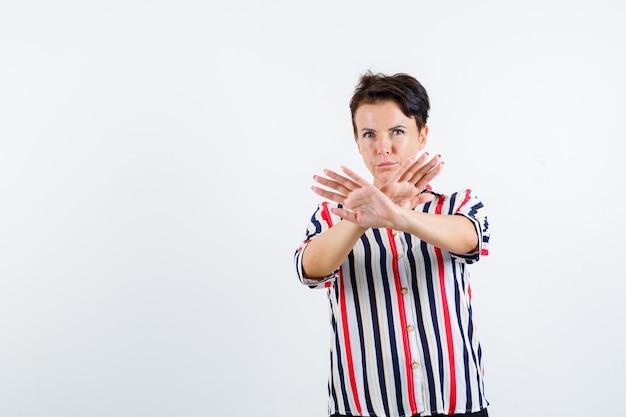 Retrato de mulher madura mostrando um gesto de parada com uma camisa listrada e olhando resoluta de frente