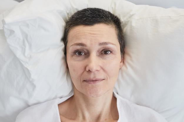 Retrato de mulher madura olhando para a câmera enquanto estava deitada na cama durante o tratamento no hospital
