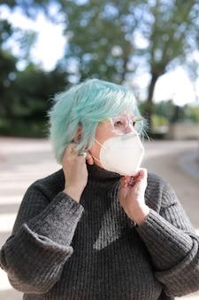 Retrato de mulher mais velha com máscara no parque