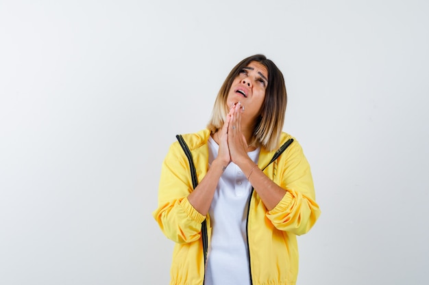 Retrato de mulher mantendo as mãos em gesto de oração com camiseta, jaqueta e vista frontal esperançosa