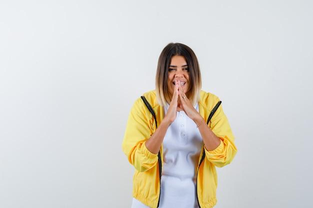Retrato de mulher mantendo as mãos em gesto de oração em camiseta, jaqueta e olhando frontalmente feliz