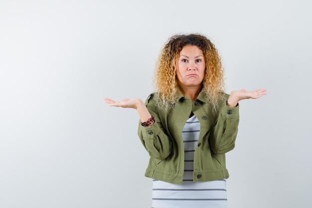 Retrato de mulher maravilhosa com as palmas das mãos de lado em uma jaqueta verde, camisa e olhando hesitante para a frente
