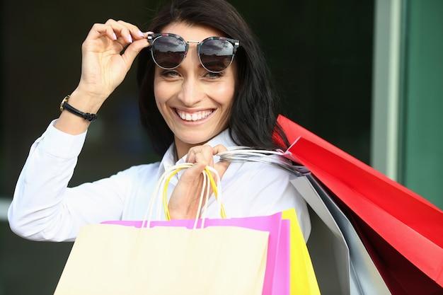 Retrato de mulher maravilhosa em elegantes óculos de sol com sacolas coloridas. mulher bonita