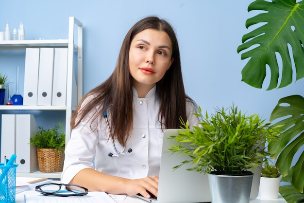 Retrato de mulher médico em sua mesa de escritório, interior do escritório