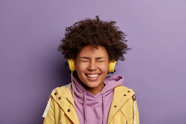 Retrato de mulher milenar étnica radiante aprecia um som agradável em fones de ouvido, ouve música popular, tem um humor otimista, sorri amplamente e se diverte com os olhos fechados