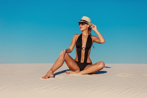 Retrato de mulher modelo bronzeada linda sexy, posando de biquíni preto, chapéu e óculos escuros na praia de areia