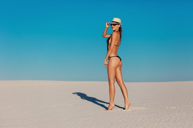 Retrato de mulher modelo bronzeada posando de biquíni preto, chapéu e óculos de sol na praia de areia