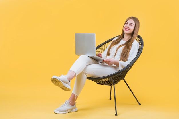 Retrato, de, mulher moderna, com, laptop, ligado, cadeira