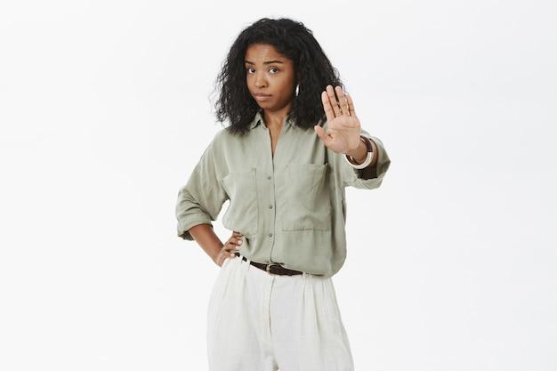 Retrato de mulher morena adulta, mandona, confiante e descontente, com cabelo encaracolado, segurando a mão na cintura puxando a palma