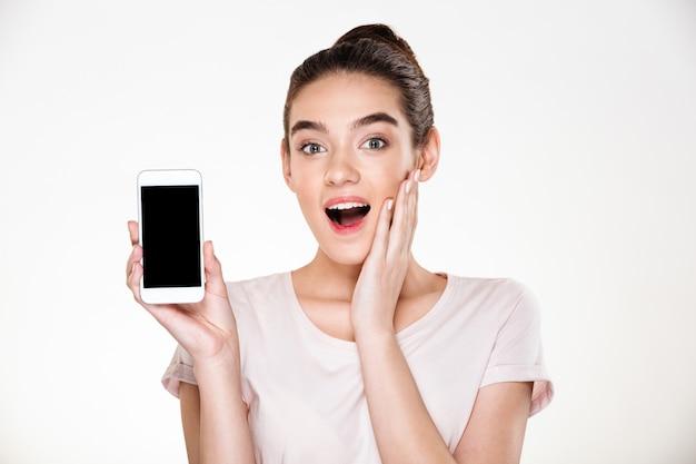 Retrato de mulher morena bem sucedida feminino, regozijando-se com sua nova exibição de smartphone moderno